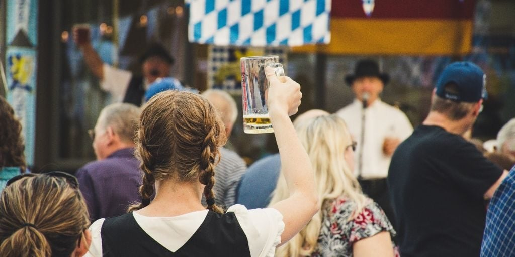 woman holding beer up at oktoberfest
