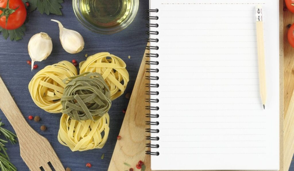 pencil and a notebook on the chopping board with some ingredients for a pasta sauce