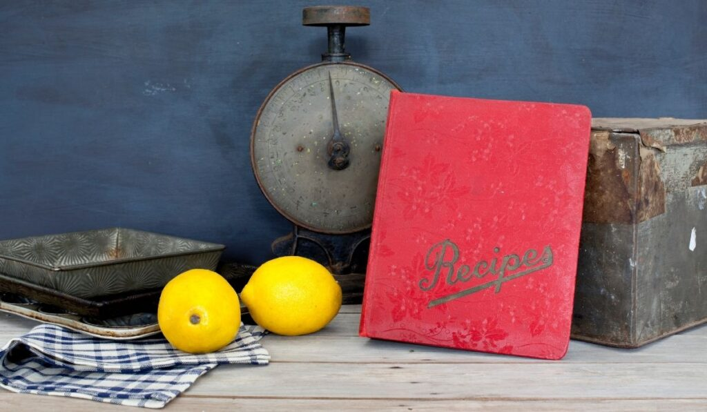 red recipe book and lemons and an old weighing scale